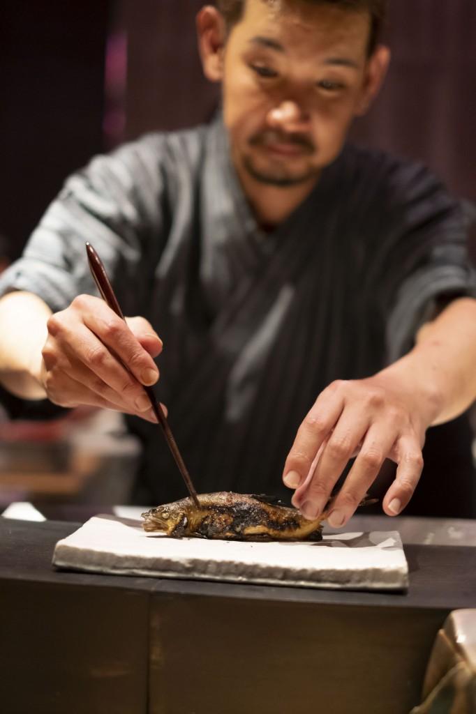 Masashi Yamada serves ayu fish